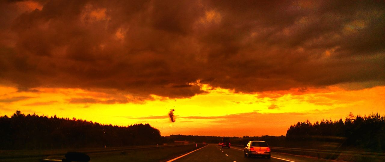 sunset, cloud - sky, dramatic sky, sky, orange color, transportation, silhouette, car, road, nature, land vehicle, tree, scenics, no people, beauty in nature, storm cloud, mode of transport, outdoors, day