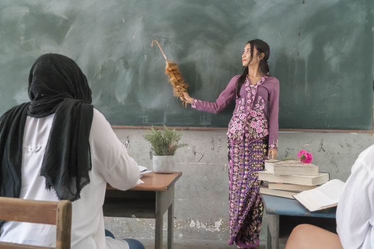 Teacher holding brush by blackboard with students sitting at table