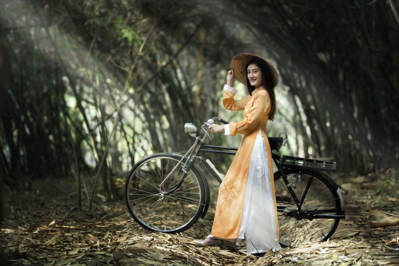 Vietnamese Women in Bamboo Garden Adult Beautiful Woman Bicycle Day Full Length Holding Land Vehicle Leisure Activity Lifestyles Mode Of Transportation One Person Outdoors Plant Sport Transportation Tree Wheel Women Young Adult Young Women