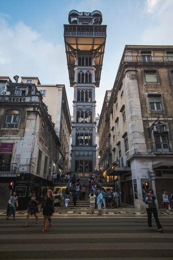 People walking on road amidst buildings in city