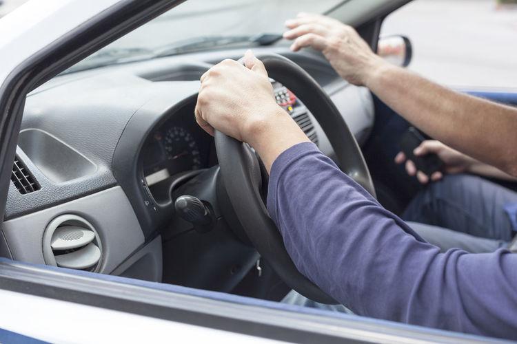 Cropped hands of men in car