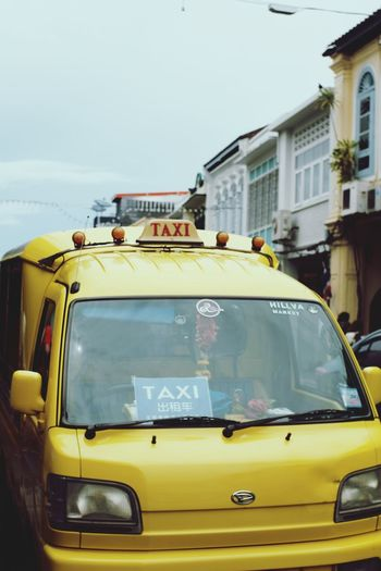 Yellow car on city street against sky