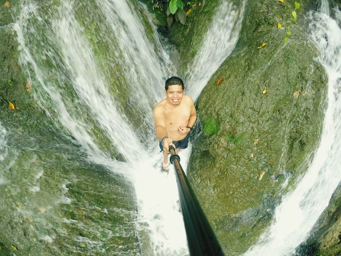 High angle view portrait of shirtless man standing amidst waterfall