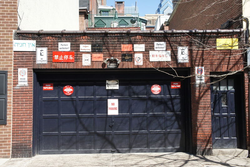 Various signs on brick wall during sunny day