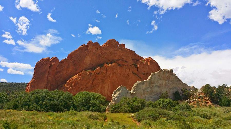 Large Rocks On Grassy Field Against Sky