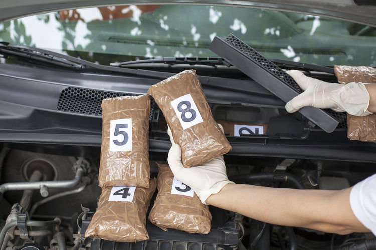 Cropped Hand Holding Cocaine Parcels In Car