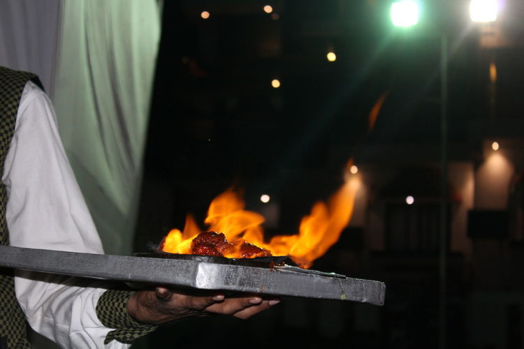 Midsection Of Waiter Holding Burning Food In Tray Restaurant