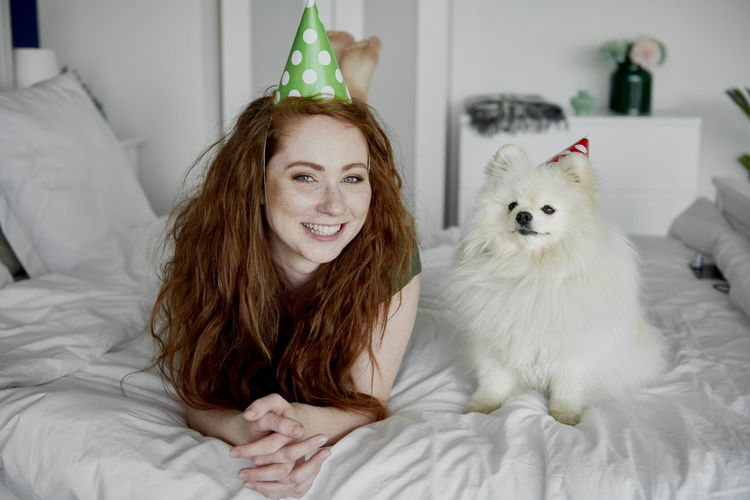 Portrait of smiling woman lying by dog on bed at home