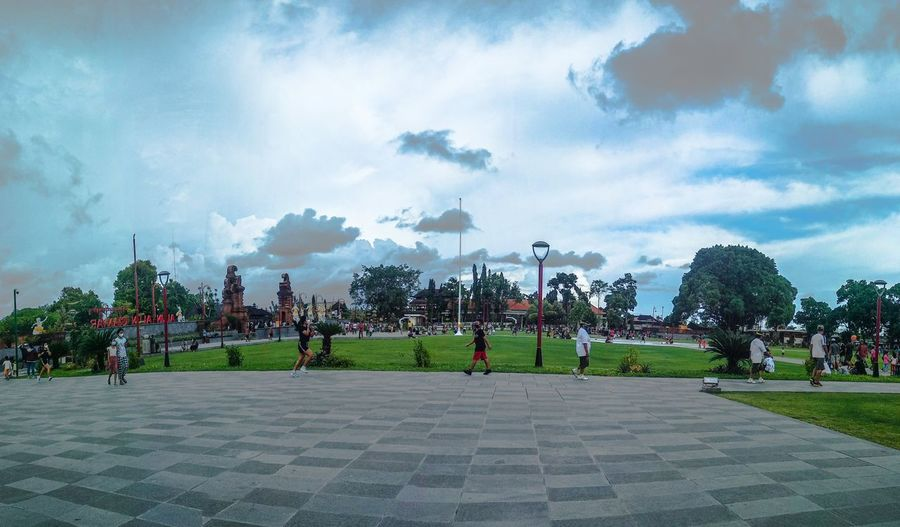 Group of people in park against cloudy sky