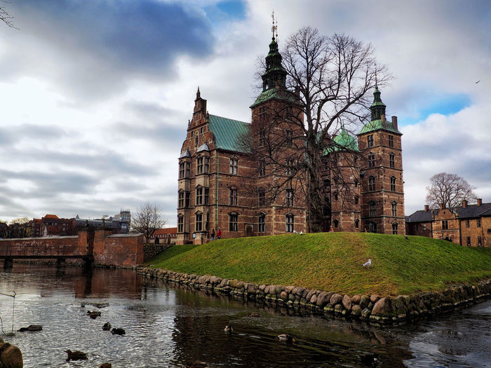 View of old building by river against sky