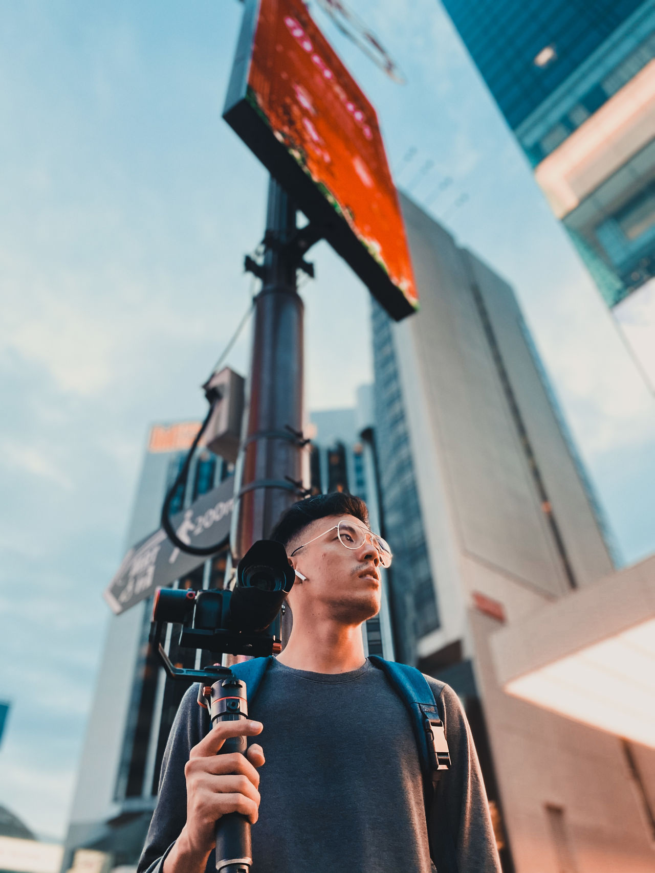 Low angle view of man holding camera standing outside buildings in city