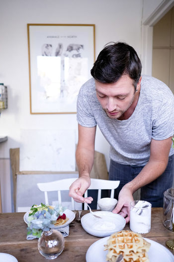 Man holding ice cream at home