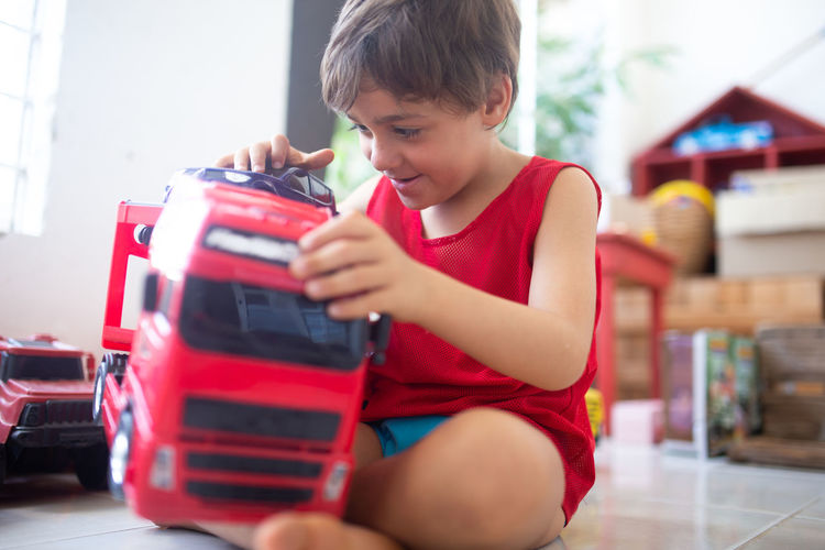 Boy playing with toy car while sitting on floor