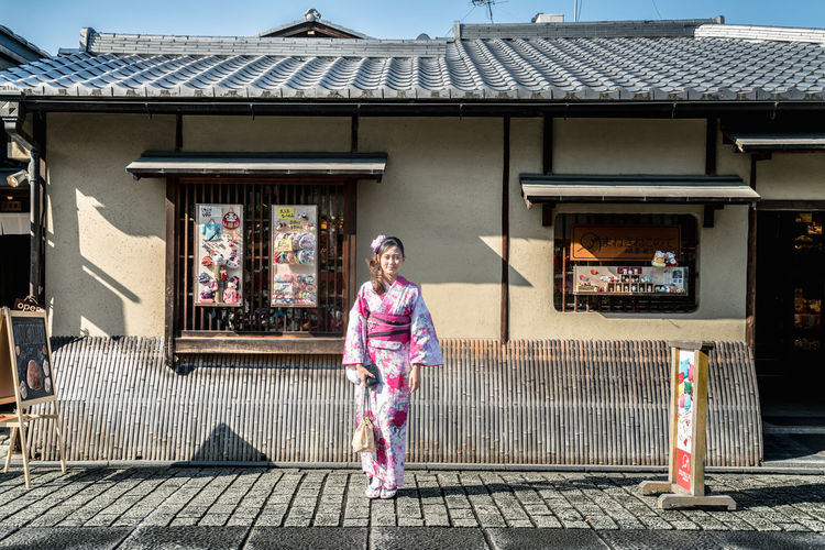 Woman Wearing Kimono While Standing On Street Against Building
