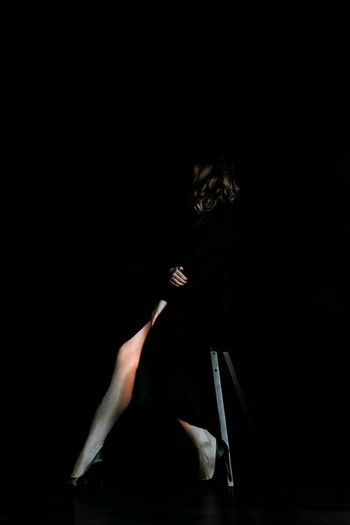 Midsection of woman holding umbrella against black background