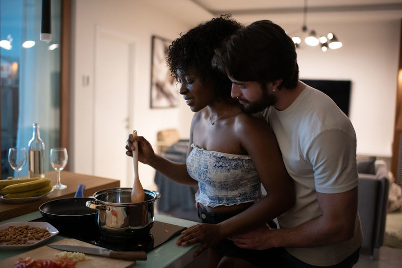 Young couple standing in kitchen at home