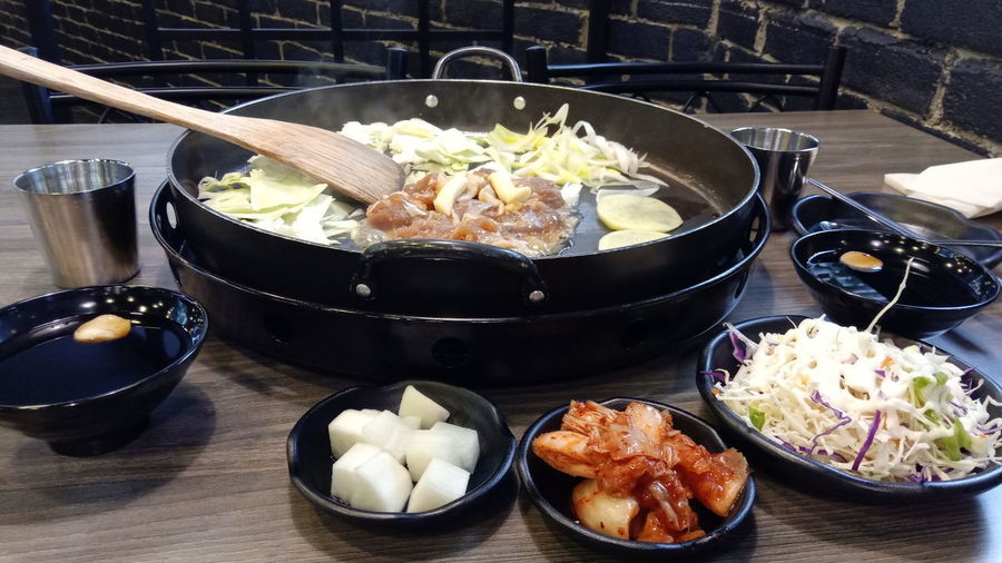 Dakgalbi Kimchi Korean BBQ Smoky Spicy Food Appetizing  Cabbage Chicken Meat Chopsticks Ethnic Food Hotplate Julienne Vegetables Korean Noodles Metal Chopsticks Platter Portions Radish Side Dishes  Smokey Using Chopsticks Wooden Spatula