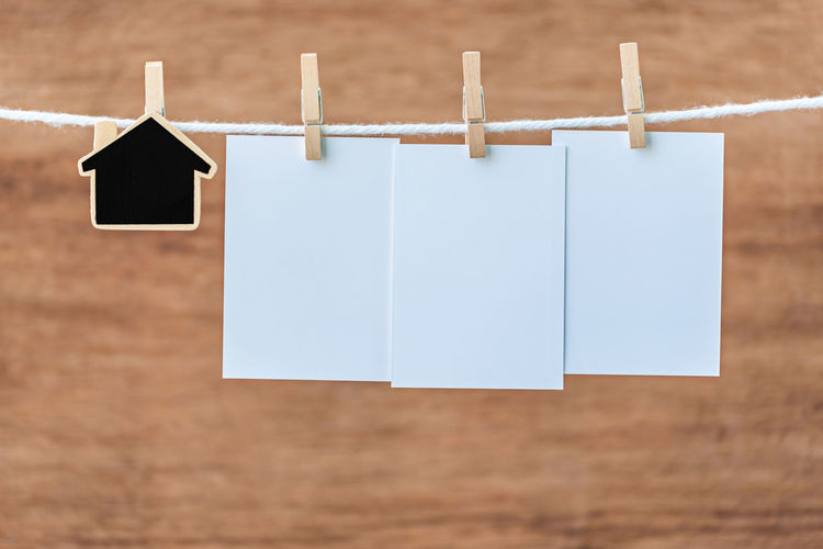 Close-Up Of Blank Notes Hanging On Clothesline Wooden Wall