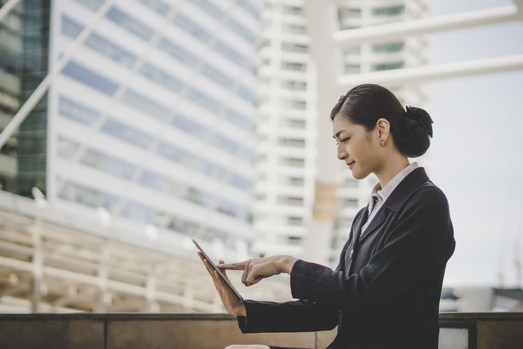 Side view of businesswoman using digital tablet while sitting against building in city