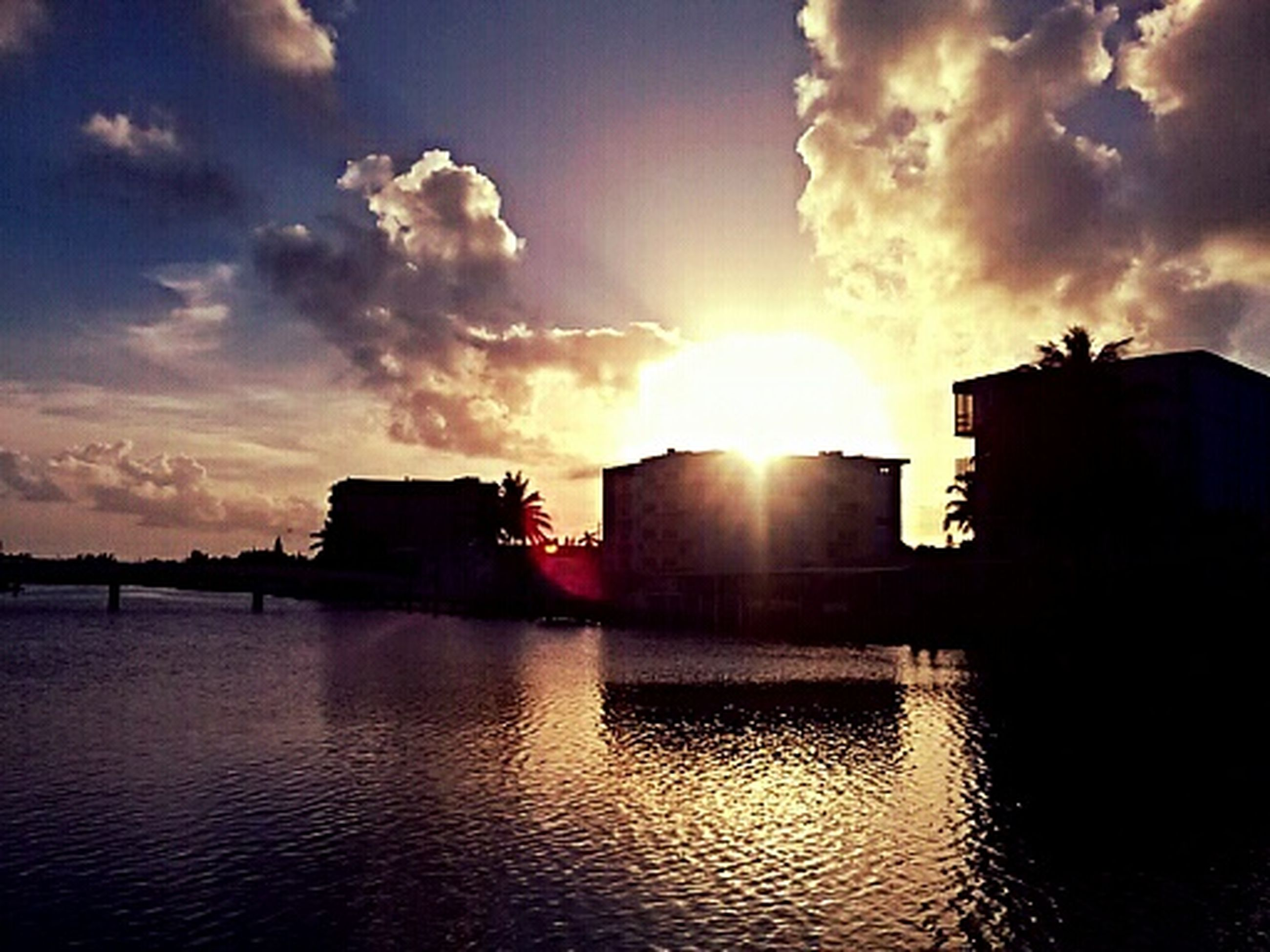 sunset, sun, building exterior, sky, architecture, water, built structure, silhouette, sunlight, reflection, waterfront, cloud - sky, sunbeam, lens flare, cloud, scenics, beauty in nature, nature, river, tranquility