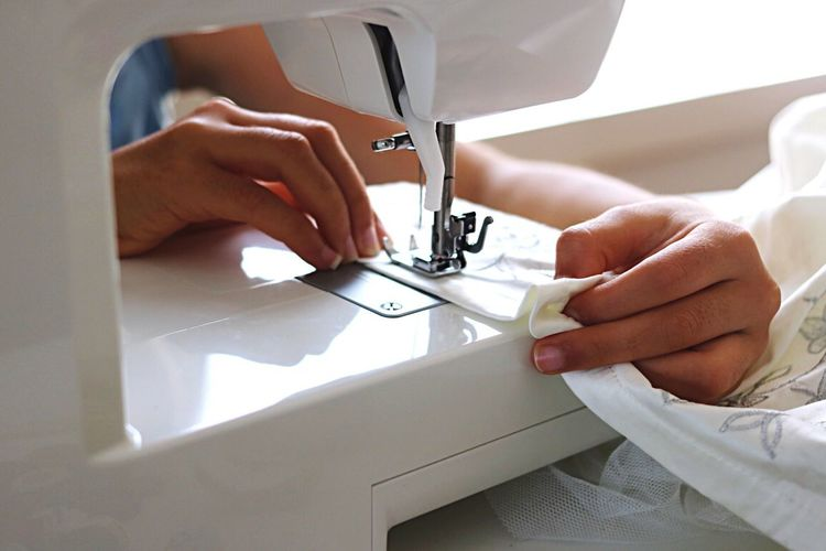 Close-up of human hand using sewing machine