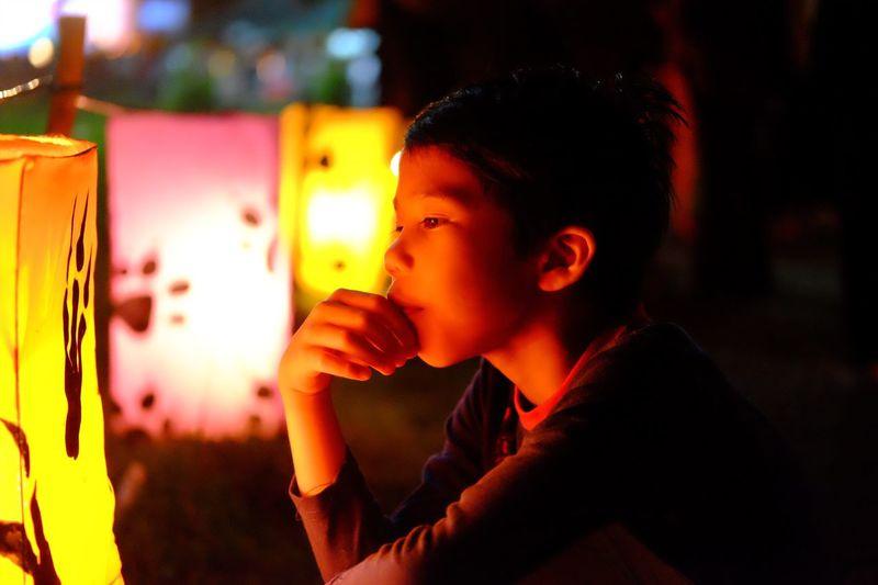 Close-Up Of Boy Looking At Illuminated Lantern
