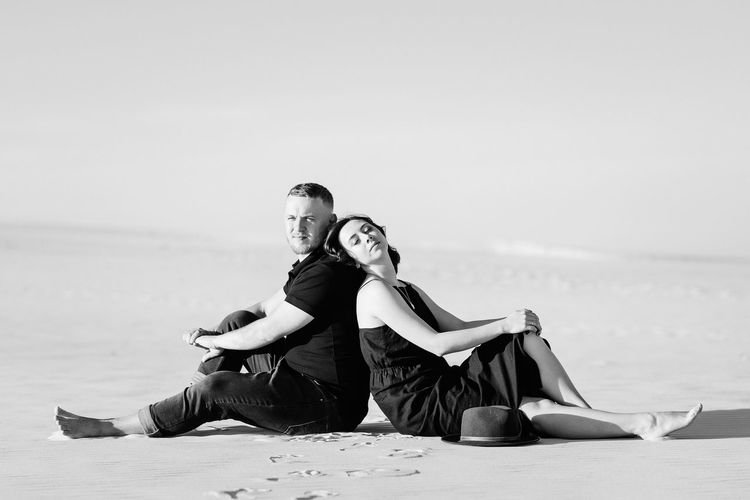 Young couple sitting on beach against sky