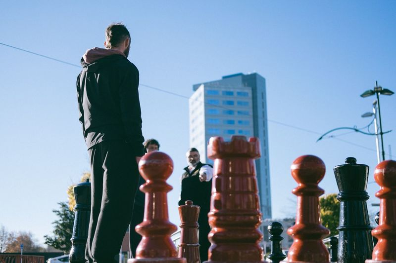 Low angle view of man on chess board against sky