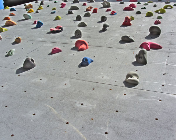 Detail of a climbing wall in a sports facility Activity Challenge Clambering Climbing Competition Crag Energy Extreme Sports Fun High Up Hill Leisure Activity Mid-air Mountain Mountain Peak Moving Up Physical Activity Playground Recreational Pursuit Rock Rock Climbing Rope Scrambling Tall Wall