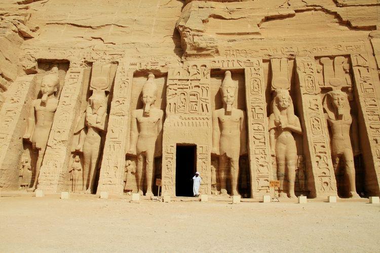 Man standing outside entrance of abu simbel temple