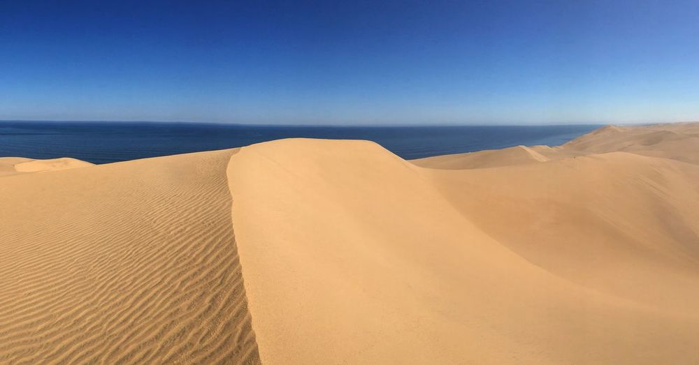 Scenic view of sand dunes against sea