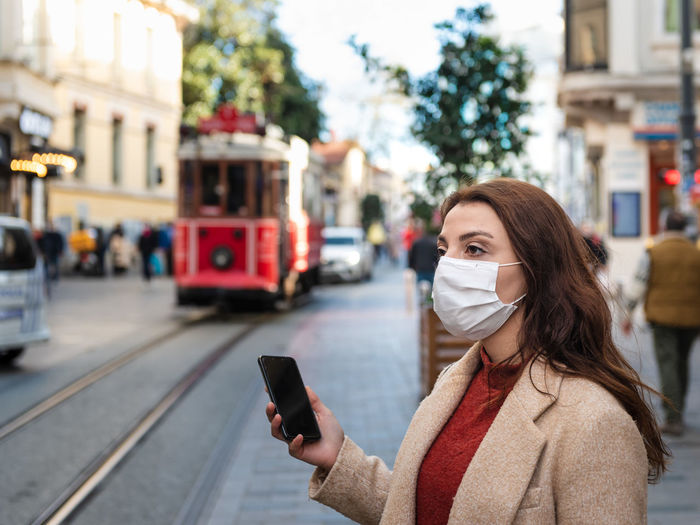 Woman wearing mask while using mobile phone while standing outdoors