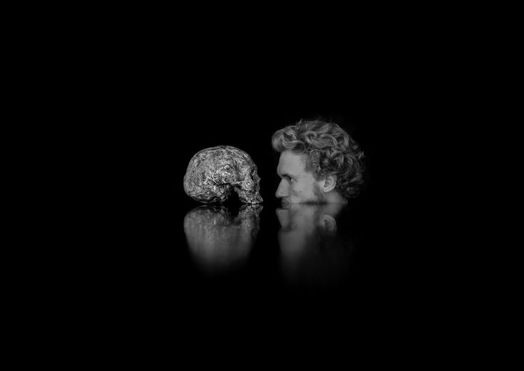 Digital Composite Image Of Man With Skull Against Black Background