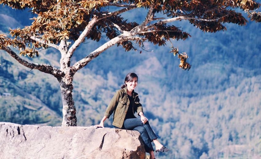 Woman sitting on tree against mountain