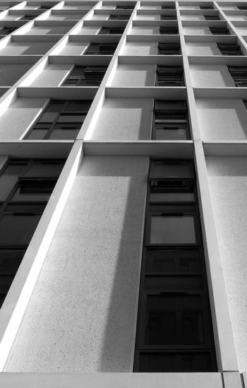 monochrome vertical view of a tall concrete angular modern high building with geometric white details