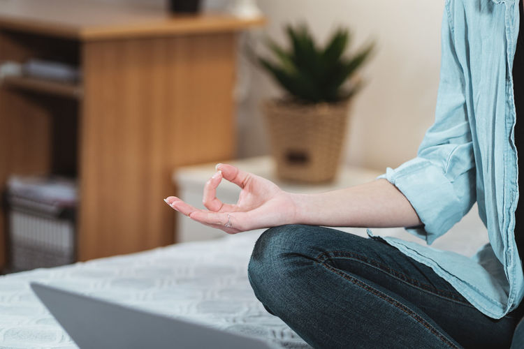 Midsection of woman meditating at home