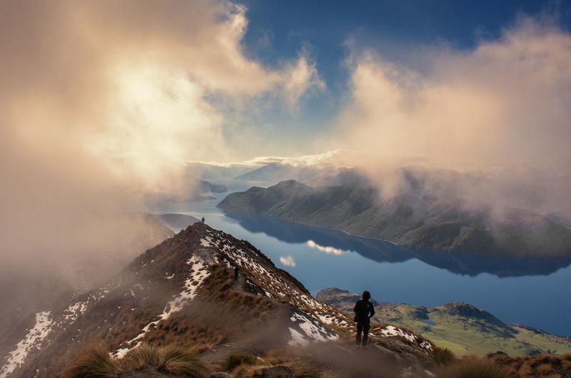 Man standing mountain ridge against sky