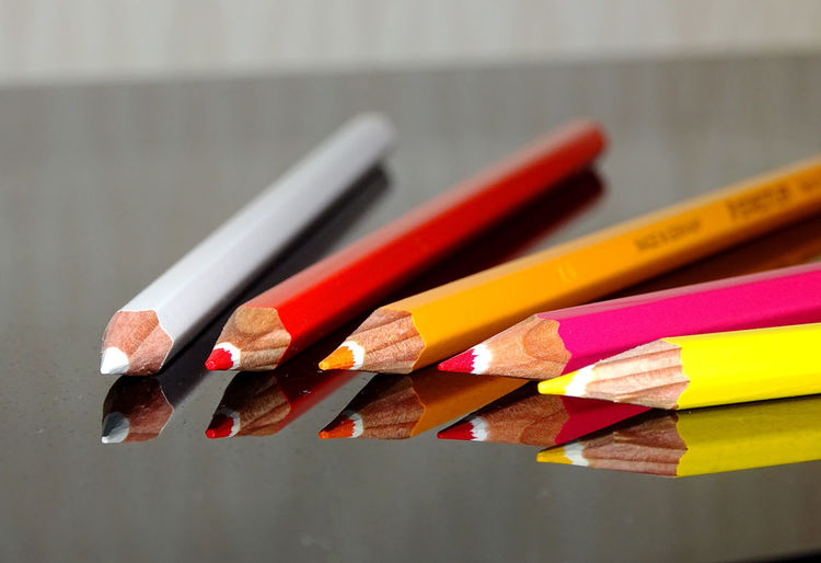 Close-up of colorful pencils on glass table with reflection