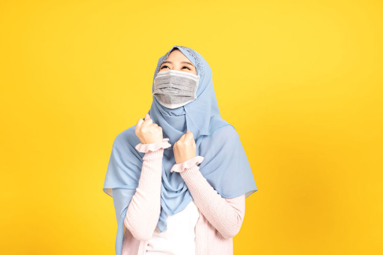 Portrait of a person standing against yellow background