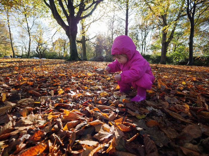 Girl crouching on field during autumn