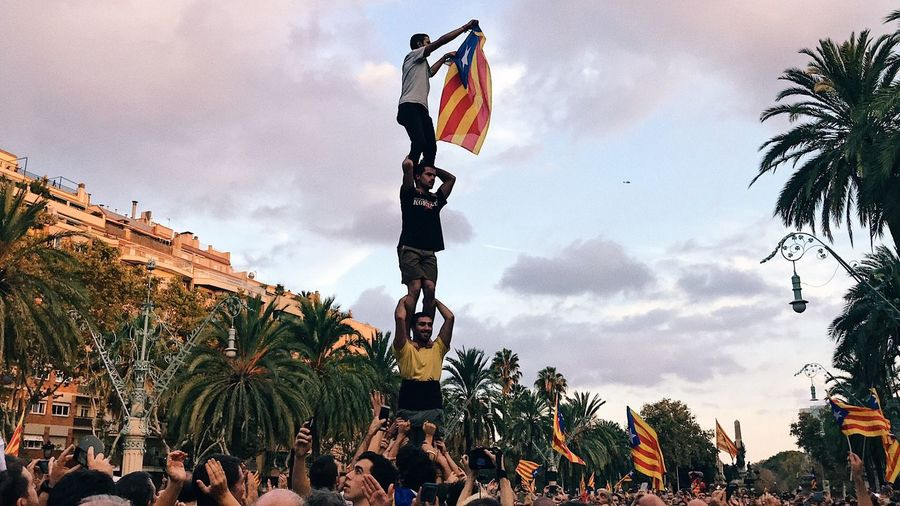 the situation in barcelona is super crazy but we're excited and happy to be fighting to build our new country let's keep it up! Flag Sky Cloud - Sky Large Group Of People Men Patriotism Tree Outdoors Day Real People Women Palm Tree Crowd Adult Adults Only People