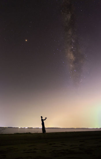 The milky way in the dark sky on the sea with muslim man on the beach. Muslim Star - Space Sky Silhouette Human Arm Standing Night One Person Beauty In Nature Arms Raised Astronomy Human Limb Space Scenics - Nature Land Limb Nature Outdoors Real People Leisure Activity Men Field