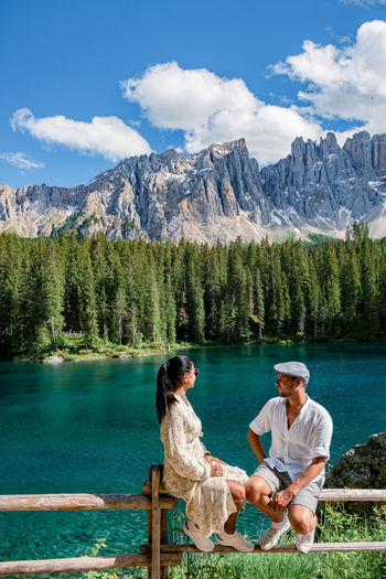 People sitting by lake against mountains
