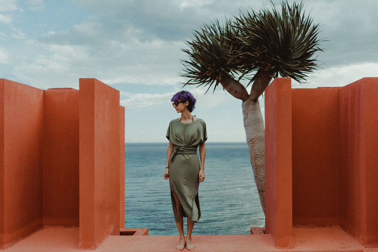 Full length of woman standing at resort against sea