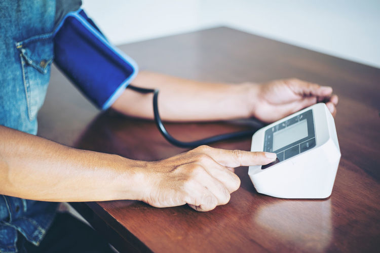Midsection of woman using blood pressure machine at table
