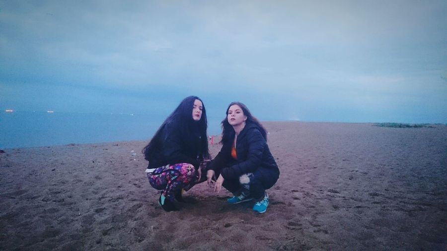 Full length of female friends crouching at sandy beach against sky during dusk