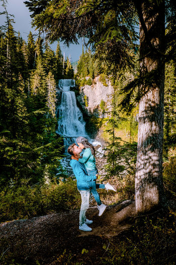 Side view of couple kissing while standing by trees in forest