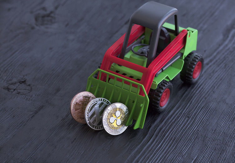 High angle view of coins with toy bulldozer on table