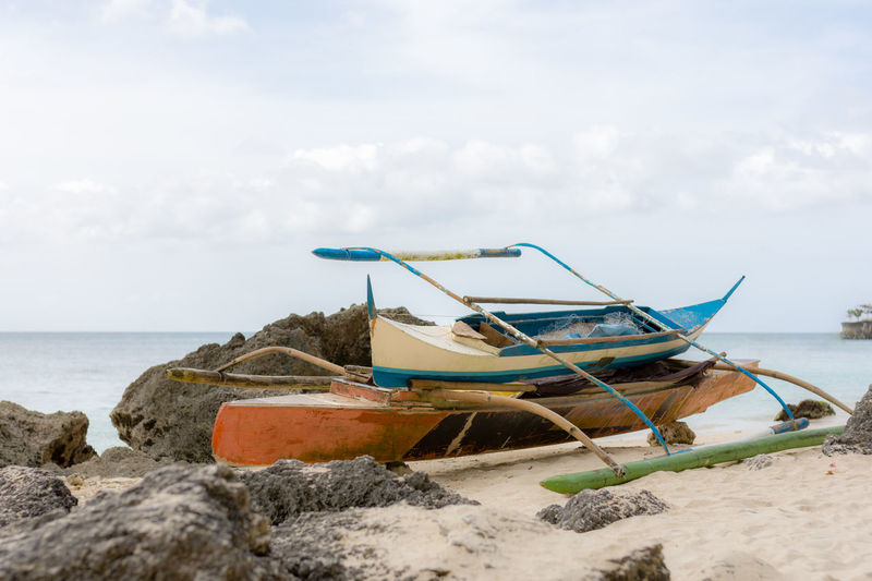 Two staked up Filipino fisherman's pump boats up on the beach protected by the rocks on a white sand beach. Beach Boat Cloud - Sky Copy Space Day Depth Of Field Filipino Fishing Boat Large Moored Nautical Vessel No People Outdoors Outrigger Protected Rocks Sand Sea Sky Small Stack Water