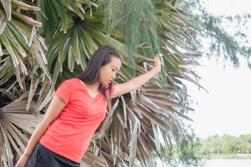 Young woman looking away while standing on palm tree